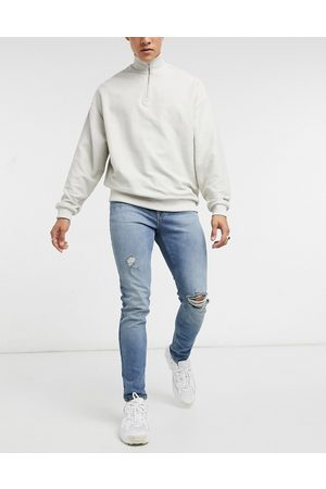 ASOS DESIGN Skinny jeans in vintage mid wash blue with knee rip and abrasions