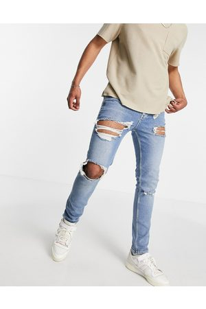 ASOS DESIGN Skinny jeans with rips and destroyed hem in vintage mid wash blue