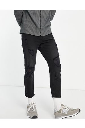ASOS DESIGN Tapered jeans in washed black with heavy rips