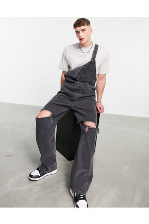 ASOS Baggy denim dungarees in washed black with knee rips