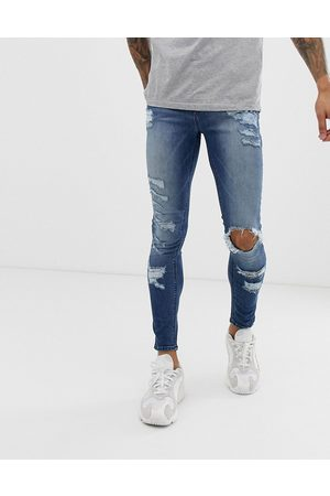 ASOS Spray on jeans in power stretch with heavy rips in mid wash blue