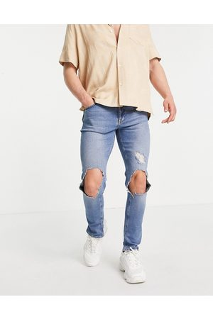 ASOS Skinny jeans with knee rips and destroyed hem in mid wash blue