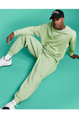 ASOS Athleisure relaxed joggers in green with health and wellbeing logo print