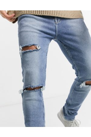 ASOS Enhanced stretch skinny jeans in vintage light wash with heavy rips-Blue