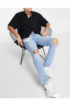ASOS Skinny jeans with heavy rips and raw hem in light wash blue