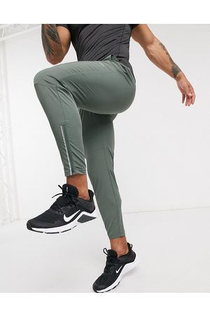 ASOS Woven skinny tapered running joggers with reflective zip detail in khaki-Green
