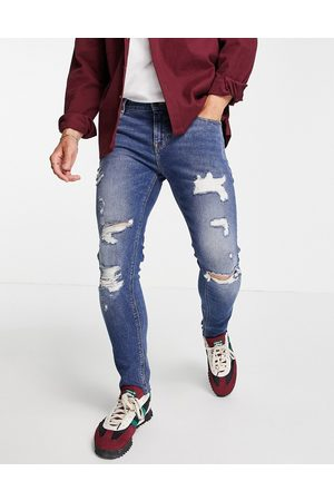 ASOS Skinny jeans in mid wash blue with heavy rips and raw hem