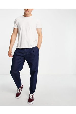 ASOS Relaxed tapered pleated jeans in dark blue