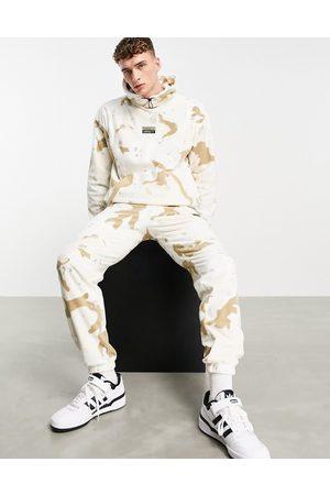 adidas RYV fleece joggers in camo print-Neutral